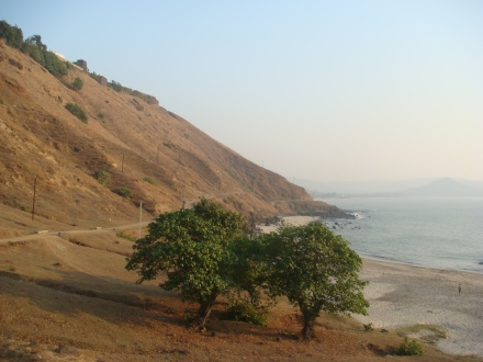 THe road hugs a cliff and the dramatic Korlai beach below