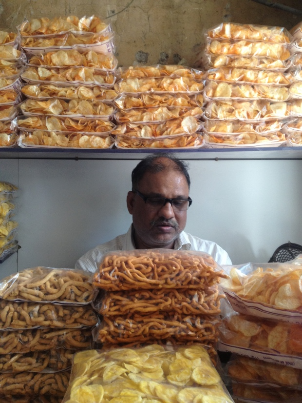 The owner of Cafe Mysore, walled in by the delicious crunchiness of South Indian snacks