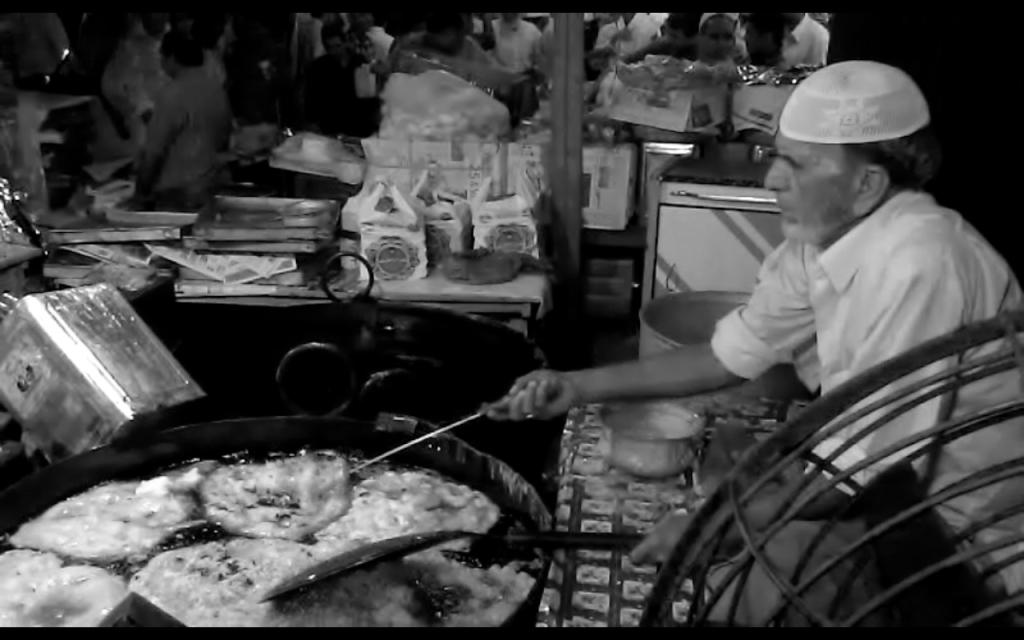 Deep fried pancakes or Malpuas floating in sea of hot ghee
